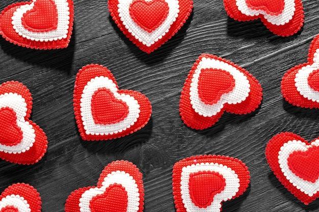 Образец красных сердец на черном деревянном фоне. любовь и концепция дня святого валентина.