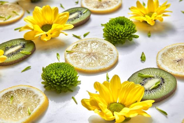 黄色、緑の花、フルーツキウイ、レモンスライス、緑の花びらからの行のパターン