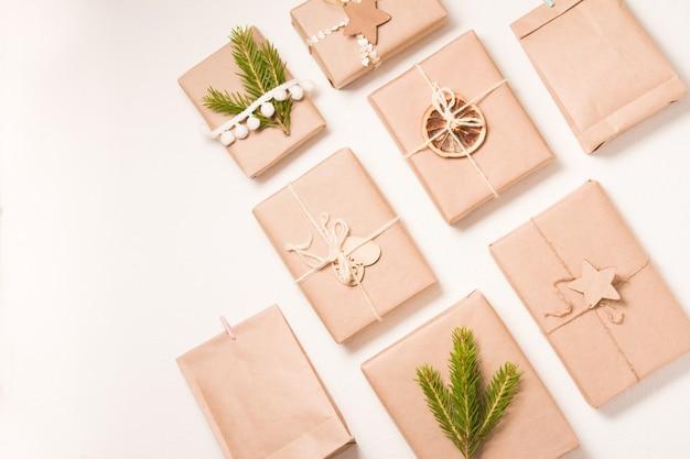 Выкройка из нескольких рождественских подарочных коробок в экологически чистом стиле на белом фоне, декор из деревянных елочных игрушек, сушеного апельсина и еловой ветки