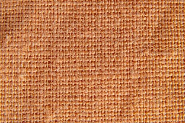 Pattern of orange or dark yellow linen fabric. macro shot