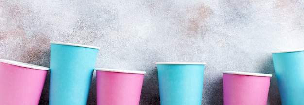 Pattern of pink and blue paper cup of coffee on old light background. zero waste concept. flat lay.