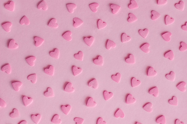 Pattern. pink confectionery hearts on pink background, texture
