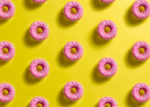 Pattern of pink donuts decorated with colored confetti with shadow on lemon yellow background