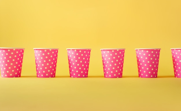 Pattern of pink polka dot paper cups on yellow background.