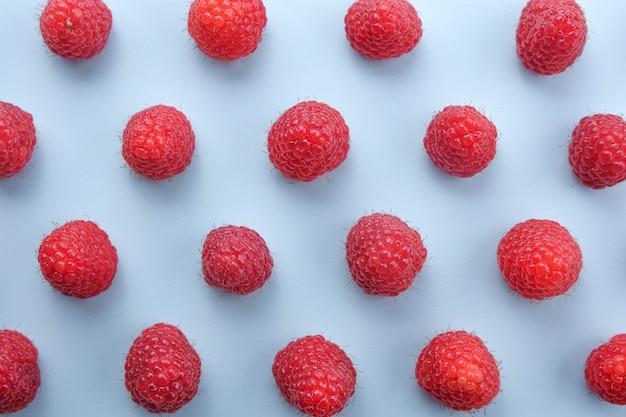 Pattern of raspberry on blue background. flat lay summer berries - red raspberries. creative minimalism