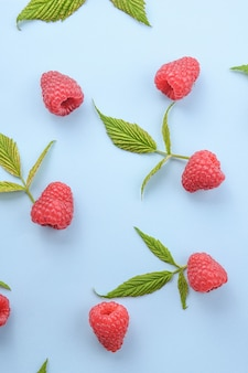 Pattern of raspberry and green leaves on blue background. flat lay summer berries - red raspberries. creative minimalism.