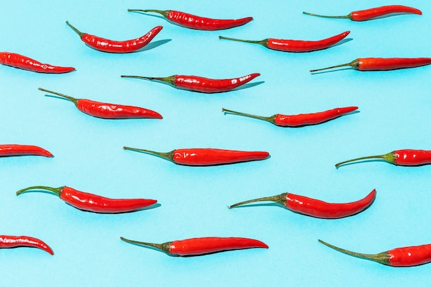 Pattern of red chili peppers on a blue background mexican food