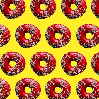 黄色の背景にペストリーを振りかける赤いドーナツのパターン