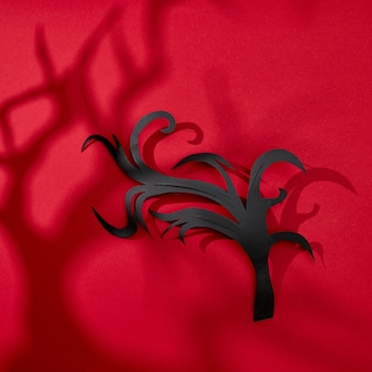 Pattern of shadows and handmade paper black branch on a red background with space for text. halloween card. flat lay