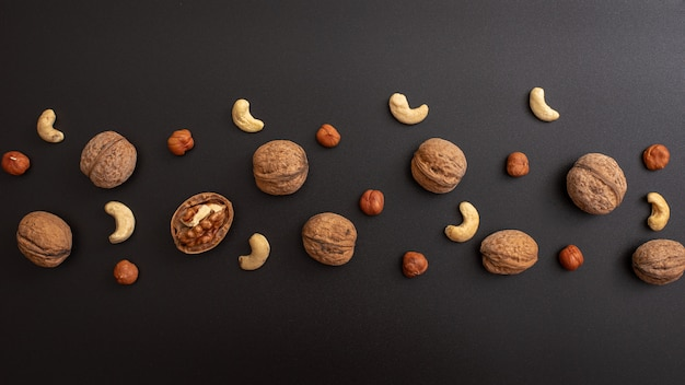 Pattern shelled walnut, hazelnut and cashews on black table.