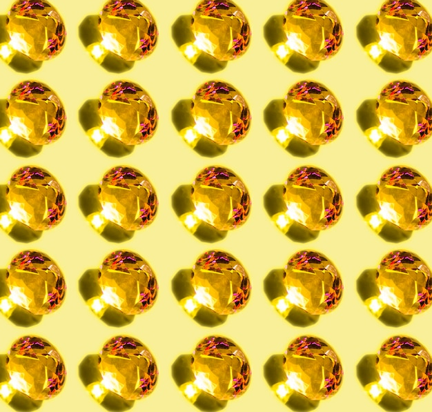 Pattern of shiny glowing diamond with shadow on yellow background