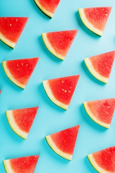 Pattern of slices of fresh slices of red and yellow watermelon on a blue . top view
