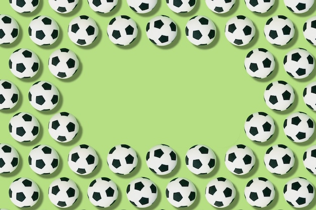 Pattern of soccer balls on a green background with copy space. football and sport concept