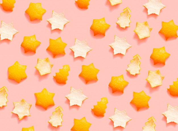 Pattern of star and christmas trees orange peel cut outs on a pink background  zero waste holidays