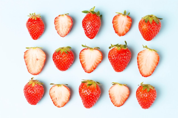 Pattern of strawberries isolated on blue background, creative background