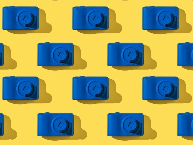 A pattern of stylish blue cameras on a yellow surface. equipment for photography.