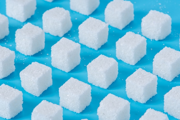 Pattern of sugar refined cubes with shadows on a blue background