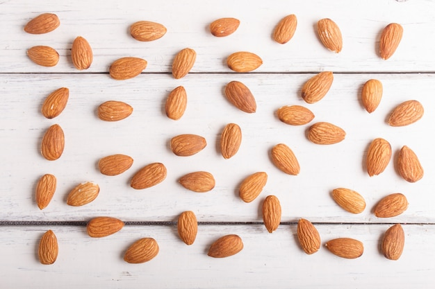 Pattern and texture made from almonds on white wooden background, flat lay.