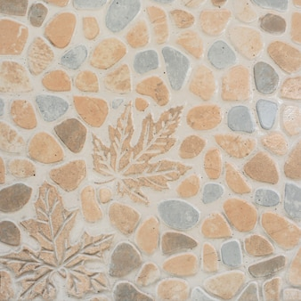 Pattern of tile with pebbles and maple leaf.