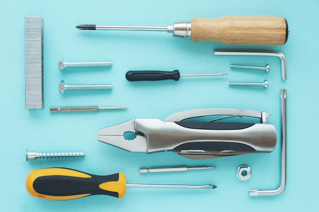 Pattern of tools: nippers, screwdrivers, keys, bolts, staples for a stapler, self-tapping screws, nut on a blue background.