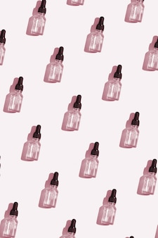 ビタミンc血清、化粧品オイルのパターン上面図スポイトボトル。物語のための垂直形式の創造的な化粧品パターンの背景