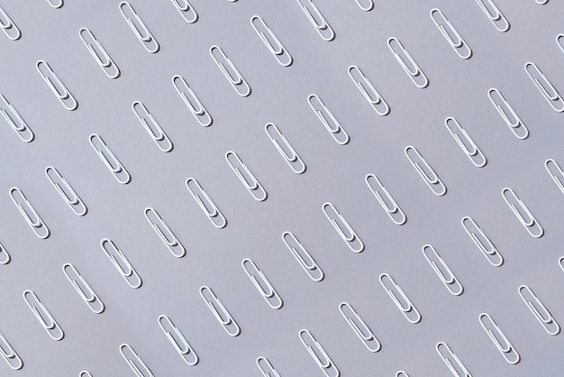 Pattern of white paper clips on grey background
