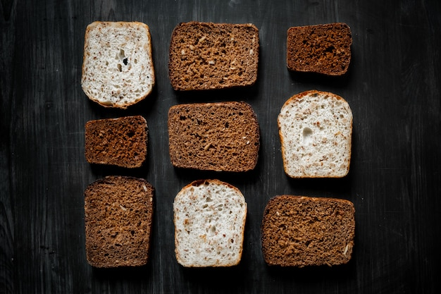 Pattern of wholemeal bread slices on dark wood surface