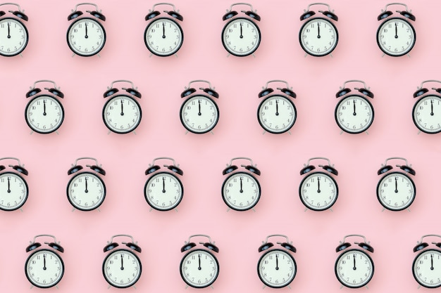 Pattern with black alarm clock on pink