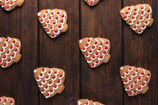 Pattern with cookies shaped christmas tree on a dark wooden background