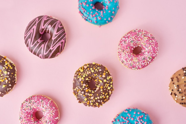 Pattern with different types of colorful donuts decorated sprinkles and icing on pastel pink surface top view flat lay