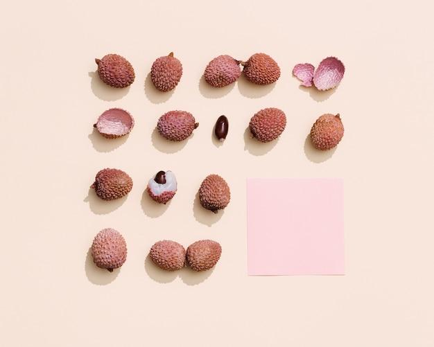 パステルベージュに新鮮なライチフルーツのパターン。最小限の果物と夏のコンセプト。上面図と日光。