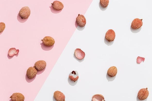 パステル ピンクの白い背景に新鮮なライチ フルーツのパターン