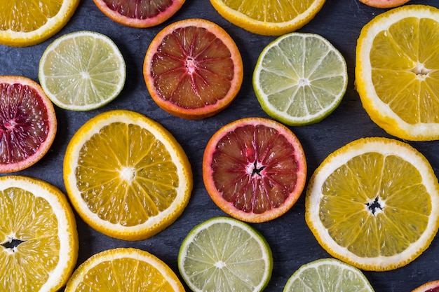 Pattern with fresh slices of different citrus fruit - yellow and red orange, lemon and lime. flat lay.