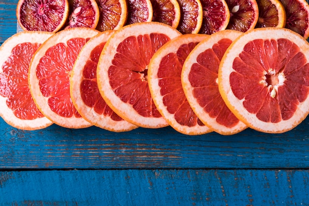 Pattern with fresh slices of grapefruit, over blue wooden board, with copy space. flat lay.