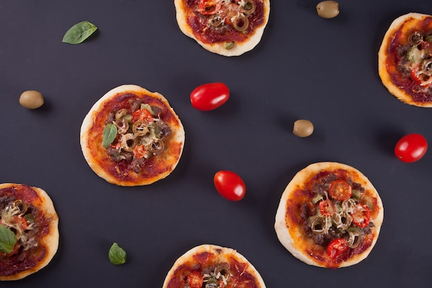 Pattern with homemade mini pizza, cherry tomatoes and green olives on black