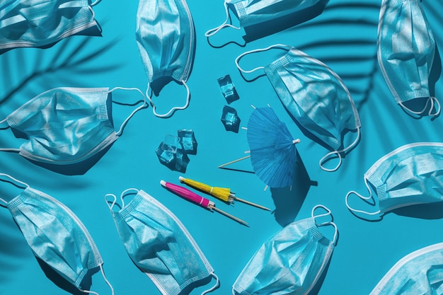 青い背景に多くの医療マスク、角氷、ビーチパラソルのパターン