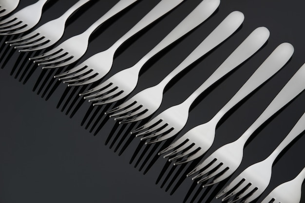 Pattern with many silver forks on black mirror background. concept,