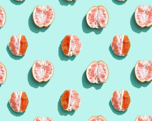 Узор с красным без кожуры апельсина или грейпфрута на фоне ярко-бирюзового цвета. концепция минимальных летних фруктов.