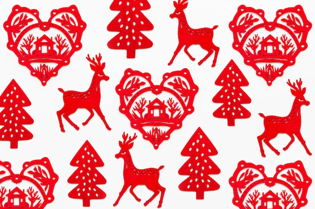Pattern with red wooden heart with silhouette of house, deer and fir tree. ornamental red christmas decoration.