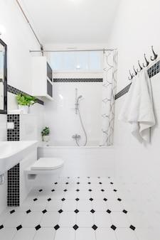 흰색과 검은색 욕실 인테리어에 무늬가 있는 바닥에는 수건, 화장실, 욕조가 있습니다. 실제 사진