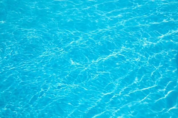 スイミングプールの水面に波打つ日光のパターン