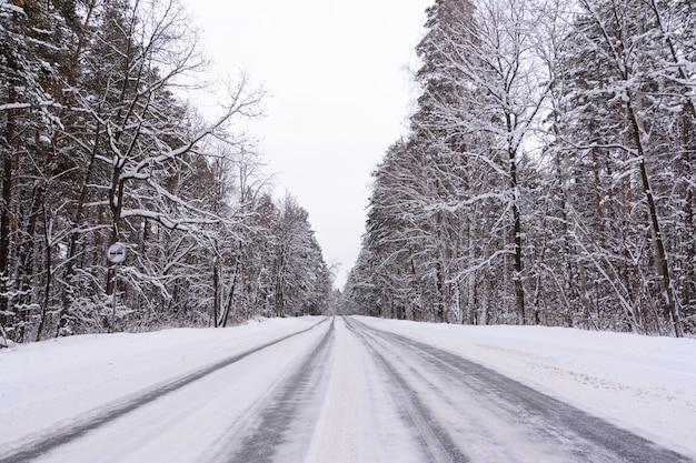 4개의 직선 형태로 된 겨울 고속도로의 패턴. 눈 덮인 숲의 배경에 눈 덮인도. 겨울 풍경입니다.