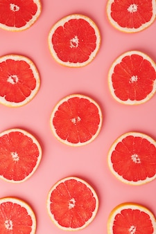 Patterns of slices of juicy grapefruit on a pink background, a beautiful pattern.
