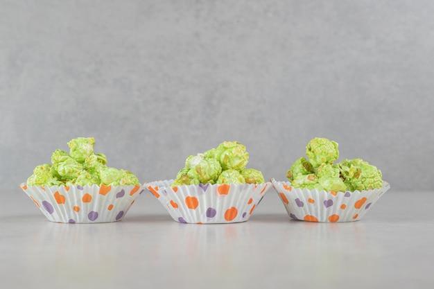 Scatolette riempite con porzioni di popcorn aromatizzate su fondo in marmo.