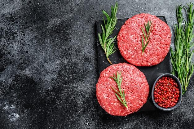 ハンバーガー用のひき肉のパテ。黒の背景。上面図。