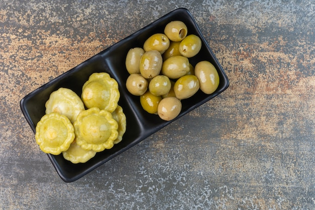 Pattypan squash and preserved olive on a dish.