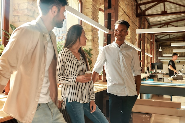 Pause at work. young and cheerful colleagues in casual wear talking about something and holding coffee cups while standing in the modern office. coffee break