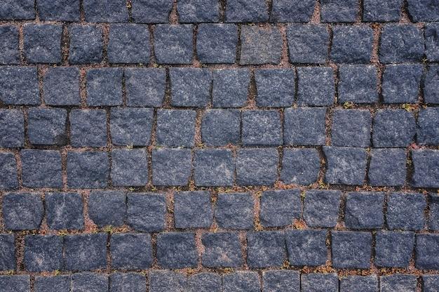 배경과 질감을 위한 포장된 도로 화강암 포장 돌로 만든 오래된 도로