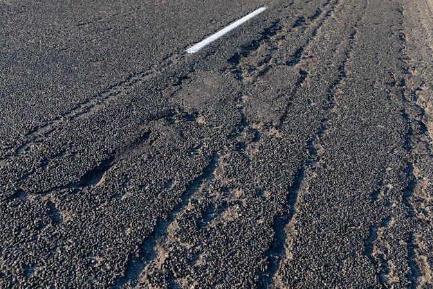 さまざまな車両の移動のための舗装道路、アスファルトに欠陥のある古い道路