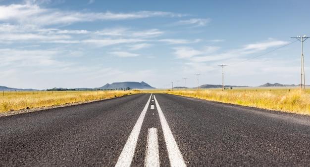 흐린 하늘 아래 남아 프리카 공화국의 마른 풍경을 통과하는 포장 된 직선 도로